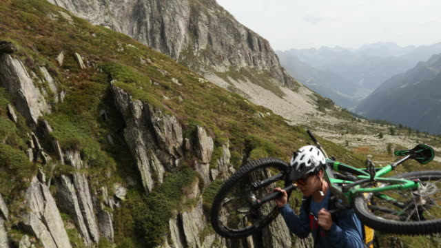 mountain biker carries bike up rmountain slope - eskapismus stock-videos und b-roll-filmmaterial