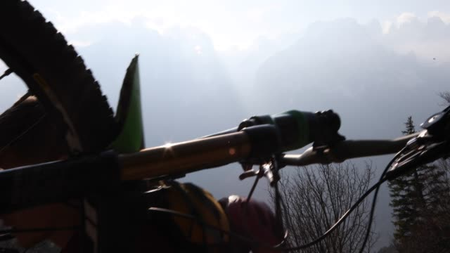 Mountain biker carries bike up steep mountain slope