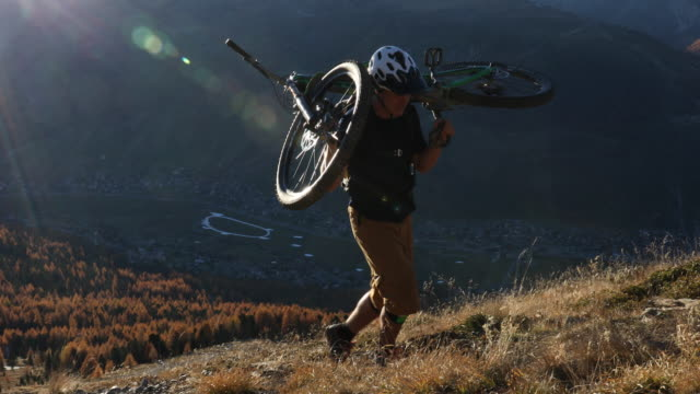 Mountain biker carries bike up steep slope above valley, mountains