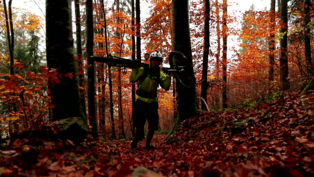 Mountain biker carries his bike up wet leafy forest path