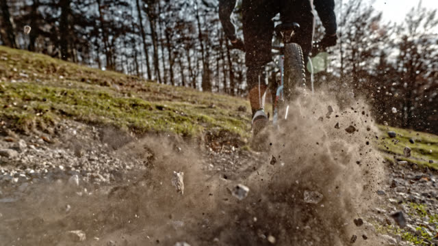 speed ramp mountain biker causing gravel to fly into the air on the gravel road in sunshine - mountain bike video stock e b–roll