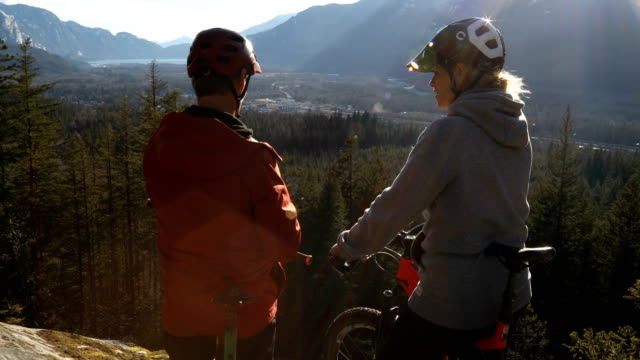 mountainbiker ehepaar pause auf der felsenplatte, um die aussicht auf die küste zu bewundern - ruhen stock-videos und b-roll-filmmaterial