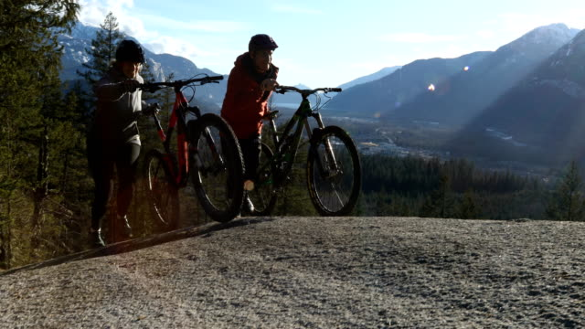 mountain biker couple push bikes up open granitic slab with dramatic view behind - vitality stock videos & royalty-free footage