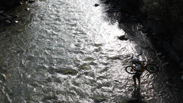 Mountain biker crosses river while holding bike, mountains