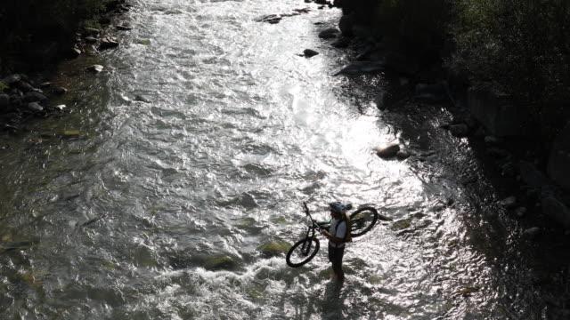 mountain biker crosses river while holding bike, mountains - 中年の男性だけ点の映像素材/bロール