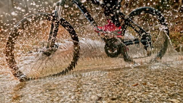 slo mo mountainbiker überqueren einen bach und die kamera spritzt - rucksack stock-videos und b-roll-filmmaterial