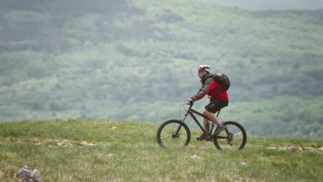 vídeos de stock, filmes e b-roll de hd: ciclismo de montanha motociclista ladeira acima - colina acima