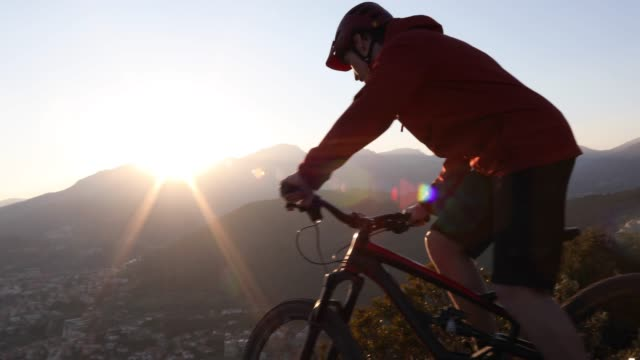 vídeos y material grabado en eventos de stock de mountain biker descends along cliff edge, looks out - casco de deportes