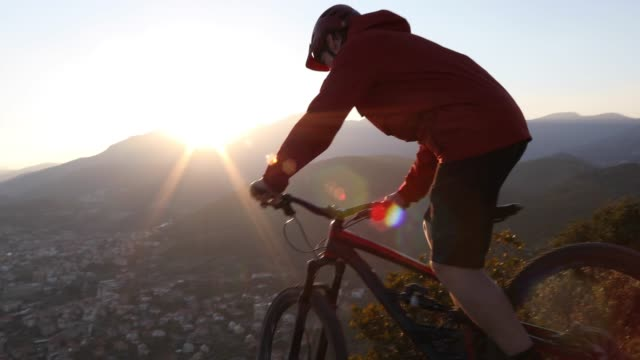 mountain biker descends along cliff edge, looks out - steep stock videos & royalty-free footage