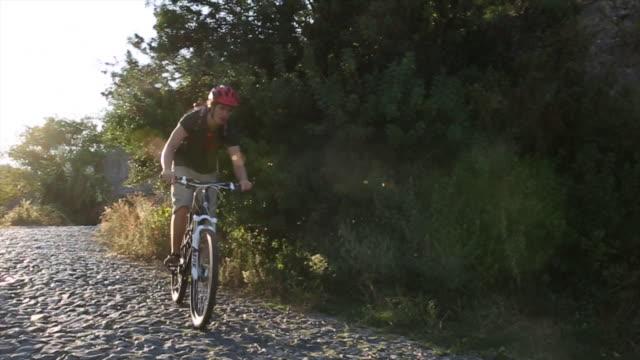mountain biker descends cobblestone path, sunrise - eskapismus stock-videos und b-roll-filmmaterial