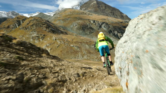 mountain biker descends high alpine trail below matterhorn - tourist stock-videos und b-roll-filmmaterial