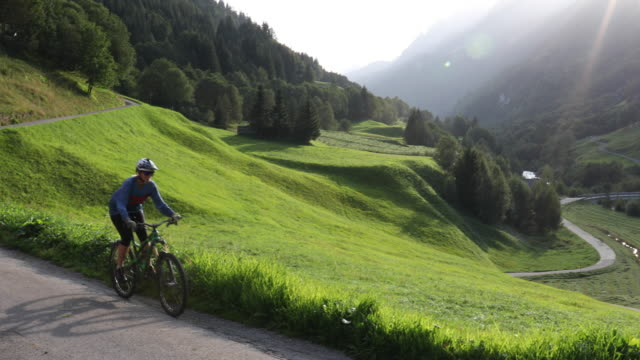 mountain biker descends road through alpine meadow, mountains - pedal pushers stock videos & royalty-free footage