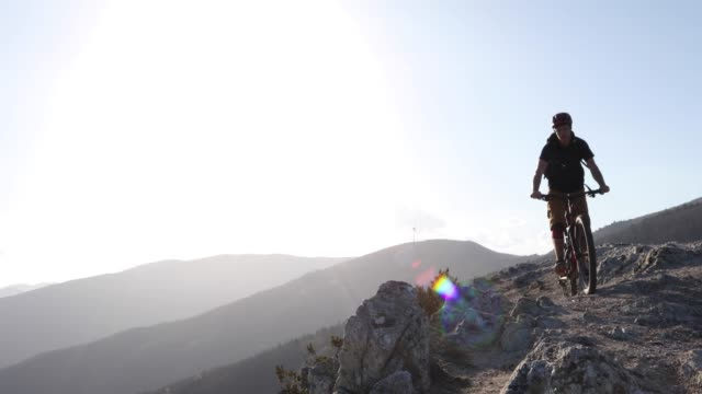 mountain biker descends rock ridge, from summit - mountain biking stock videos & royalty-free footage