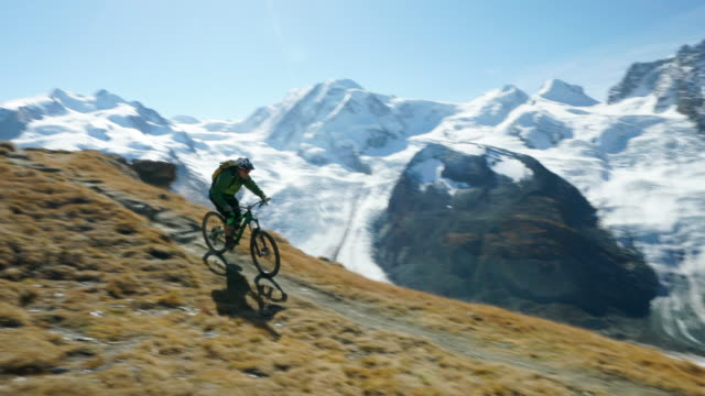 Mountain biker descends rocky trail below Matterhorn, view of glacier