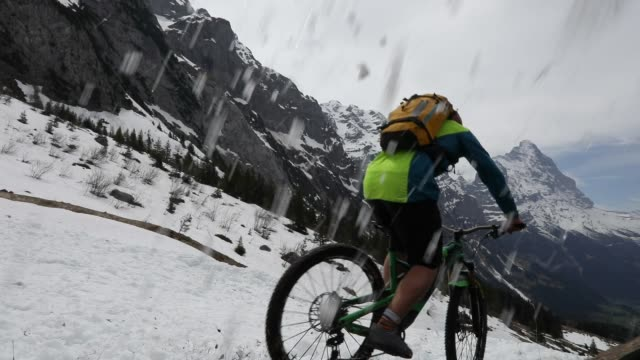 mountain biker descends snow slope, in mountains - andare in mountain bike video stock e b–roll