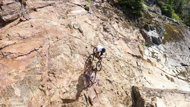 mountain biker descends steep long rock face on mountain side - felswand stock-videos und b-roll-filmmaterial