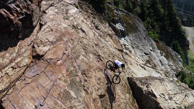 mountain biker descends steep long rock face on mountain side - rock face stock videos & royalty-free footage