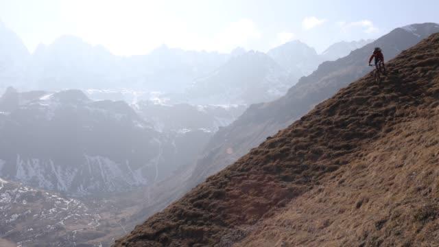 vidéos et rushes de mountain biker descends steep mountain slope - vtt