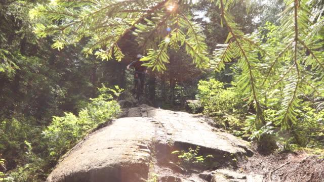 マウンテンバイカーは、森の中で急な岩のスラブを下ります - しゃがむ点の映像素材/bロール