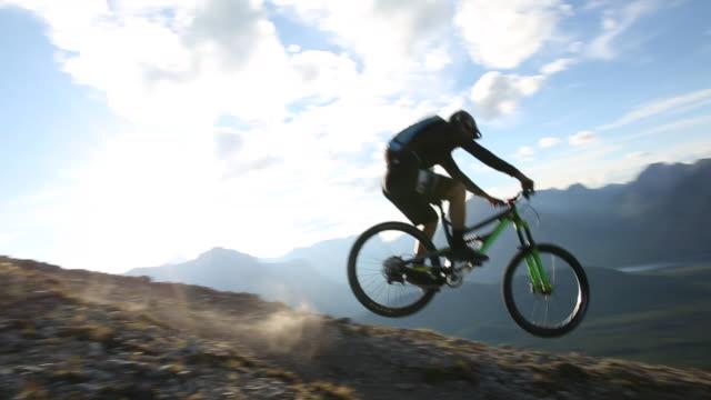 Mountain biker descends steep slope, from ridge crest