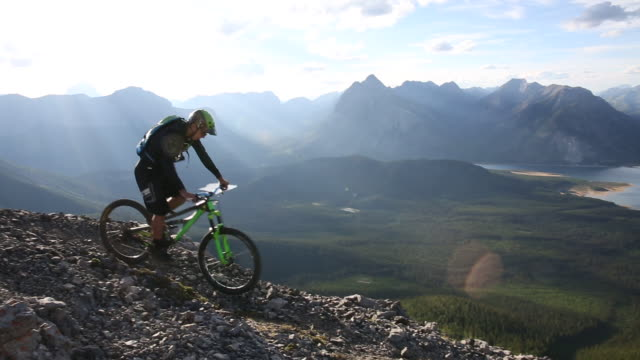 mountain biker descends steep slope, from ridge crest - steep stock videos & royalty-free footage