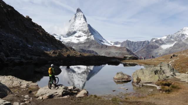 Mountain biker descends to lake edge, below Matterhorn
