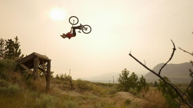 A mountain biker does a jumping back flip trick off a ramp.