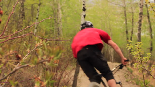 a mountain biker does a trick on a dirt trail. - slow motion - マウンテンバイク点の映像素材/bロール