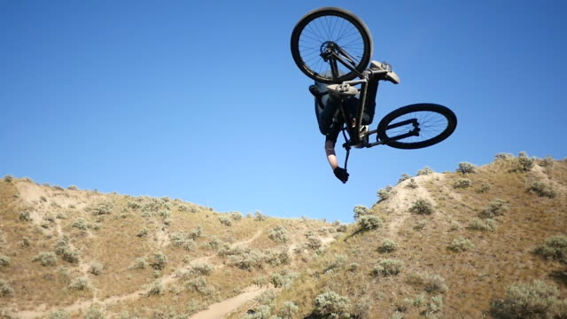 a mountain biker does a trick on a dirt trail. - mountain bike video stock e b–roll
