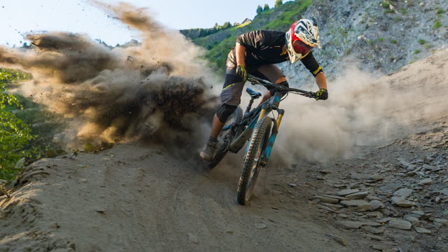 マウンテン バイク コーナーで漂流、ダウン彼のフィートを植え、背後にある塵の雲を残して - マウンテンバイキング点の映像素材/bロール