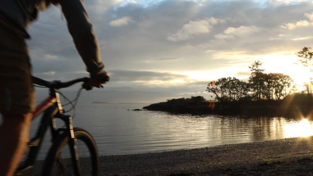 Mountainbike-åkaren utforskar beach kusten vid soluppgången