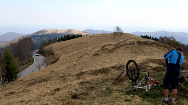 Mountain biker fixes puncture on grassy hilltop