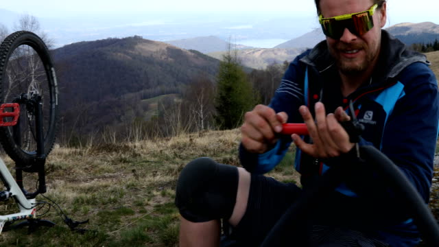 mountain biker fixes puncture on grassy hilltop - inner tube stock videos and b-roll footage