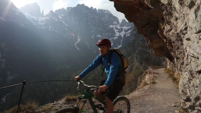 Mountain biker follows trail on mountain ledge