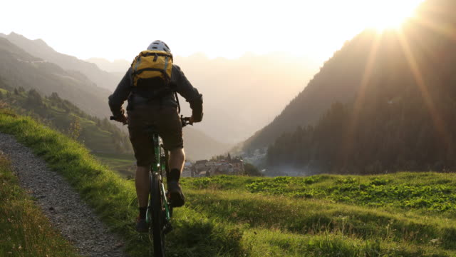 mountain biker gains track above distant mountain ranges - mountain bike video stock e b–roll