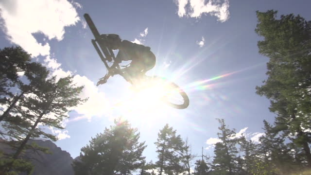 A mountain biker going off jumps in a forest on a mountain. - Slow Motion