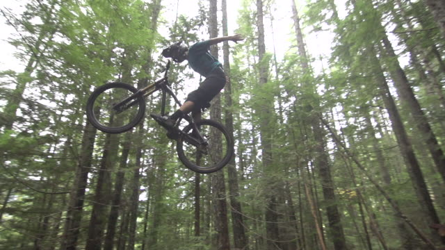 vídeos de stock e filmes b-roll de a mountain biker going off jumps in a forest on a mountain. - super slow motion - filmed at 240 fps - andar de bicicleta de montanha