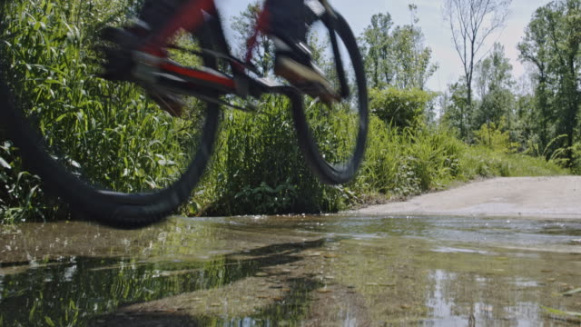 slo mo mountain biker jumping into a puddle - mountain bike stock videos & royalty-free footage