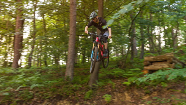 mountain biker jumping off cliff on dirt trail, doing a stunt - horseback riding stock videos & royalty-free footage
