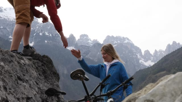 mountain biker lends companion a helping hand - assistance stock videos & royalty-free footage
