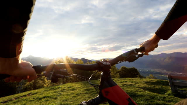 mountain biker looks out at view as sun rises above snow capped mountains - cycling helmet stock videos & royalty-free footage