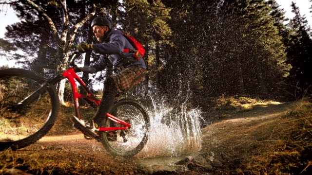slo mo mountain biker making a splash riding through a puddle in the forest - mountain biking stock videos & royalty-free footage