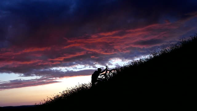 Mountain biker moving up at sunset-slow motion