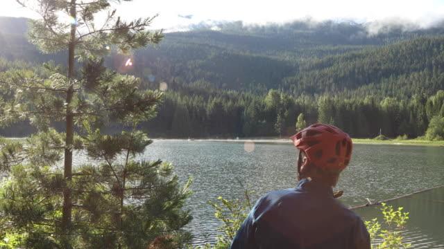 vídeos de stock e filmes b-roll de mountain biker pauses at lake's edge to look off to scene ahead - capacete de desporto