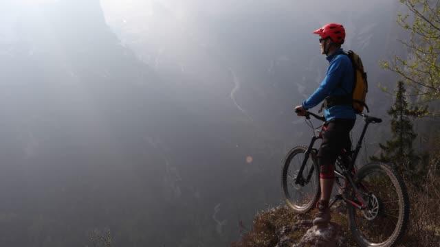 mountainbiker hält, in der ansicht von vorgebirge zu nehmen - mountainbiking stock-videos und b-roll-filmmaterial