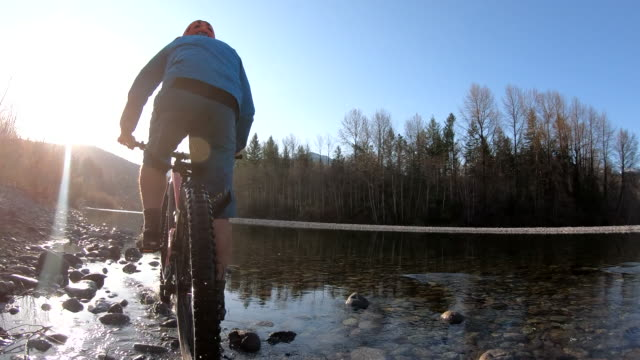 mountain biker pedals upstream in river shallows - mountain bike stock videos & royalty-free footage