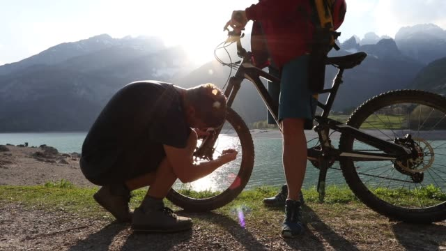 mountain biker performs bike repairs on trail, sunrise - mountain biking stock videos & royalty-free footage