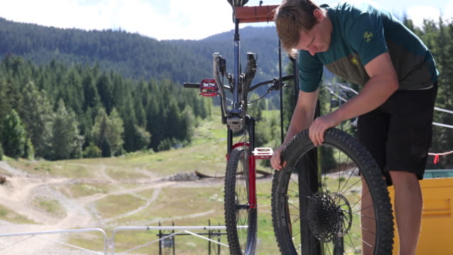 stockvideo's en b-roll-footage met mountain biker voert reparaties bij bike work stand - rijwiel