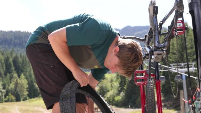 stockvideo's en b-roll-footage met mountain biker voert reparaties bij bike work stand - piercen