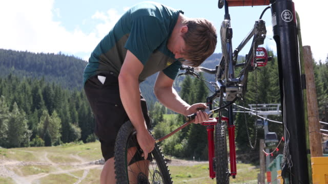 stockvideo's en b-roll-footage met mountain biker voert reparaties bij bike work stand - autoband